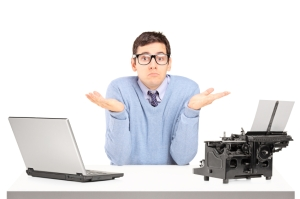 Confused young man with a laptop and typing machine on a table
